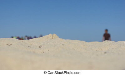 View of tanned man walking among sand, close-up