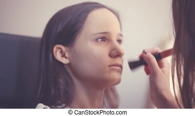 Makeup artist makes a young woman beautiful makeup before an...