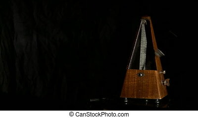 View of metronome sets rhythm. Musician slows it, close-up