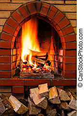 woods pile and burning firewood in brick fireplace - pile of...