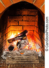 ash, coal and burning wooden logs in fireplace in country...