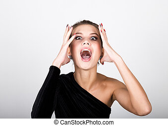 close-up fashion photo young lady in elegant black dress, playful woman caught himself with his hands behind his head and shouts