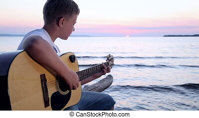 boy plays on guitar at sunset