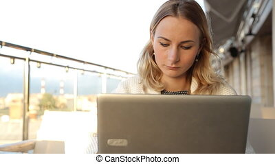 Woman online shopping via laptop in cafe.