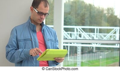 Programmer in glasses using his tablet computer at modern...