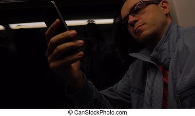 Serious man wearing glasses reads text on his smartphone in...