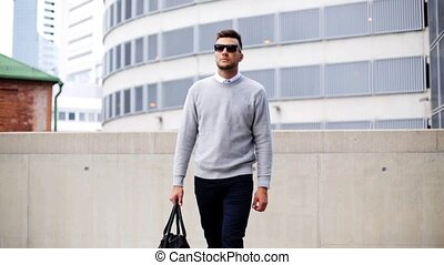 young man with sunglasses and bag walking in city