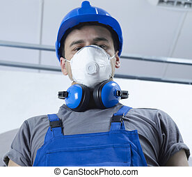 Construction worker with protective equipment looking at...