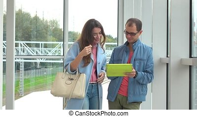 Smiling man and young woman using tablet computer at modern...
