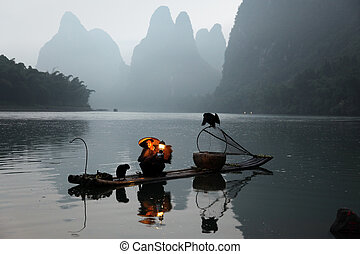 Chinese man fishing with cormorants birds in - YANGSHUO -...