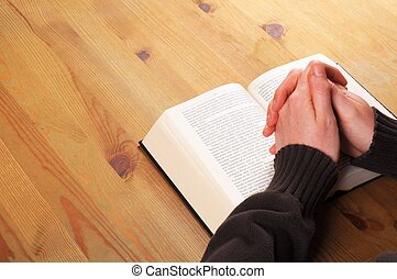 praying hands and book showing christian religion concept