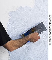 Construction worker plastering a wall