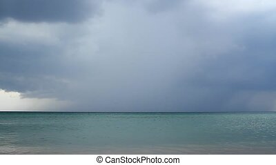 Above the beach begins thunderstorm - Above the water,...
