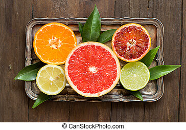 Fresh citrus fruits with leaves on a  wooden table