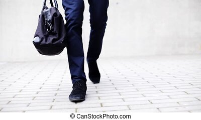 young man with bag walking along city street - business,...