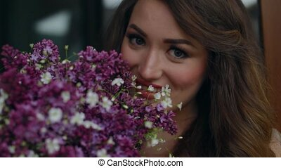 The bride holding a bouquet and inhales the fragrance of...