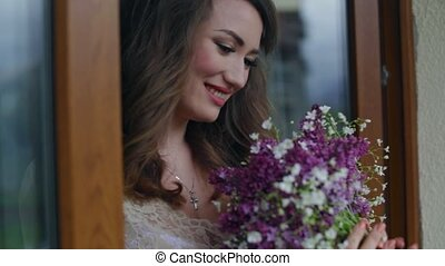 The bride holding a bouquet and inhales the fragrance of flowers