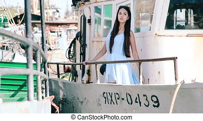 Young girl at the stern of the old vessel. Girl posing on...