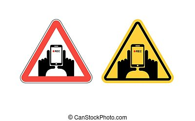Warning sign of attention vertical video. Dangers yellow sign hand and smartphone. Set of road signs against shooting on phone. Note vertical record