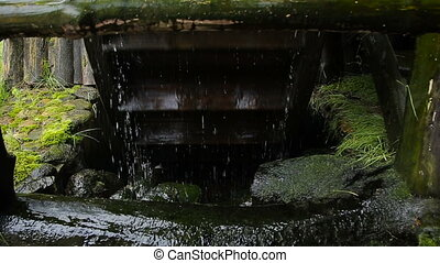 Working watermill wheel with falling water