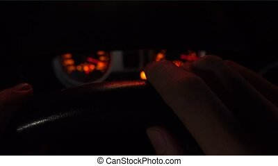 Man driving at night. 4K close up shot of hands on the steering wheel, top view