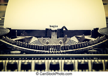 """Words """"begin"""" written with old typewriter on white paper in..."""