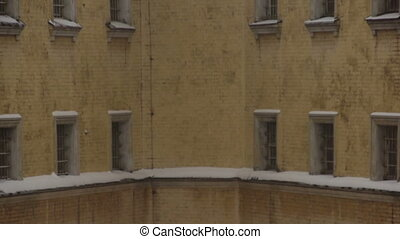 Fragment of old prison building in winter - Windows of old...