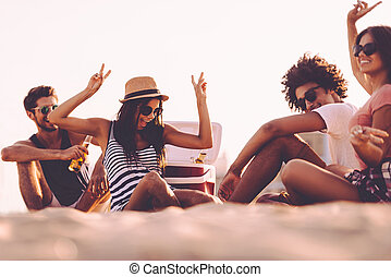 Enjoying beach party. Cheerful young people spending nice...