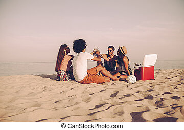 Cheers to friends! Cheerful young people spending nice time...
