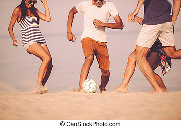 Beach ball with friends Cropped image of young people...