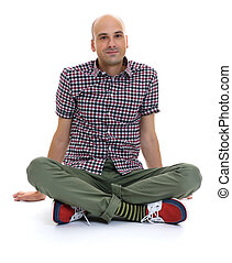 casual bald man sitting with legs crossed isolated on white