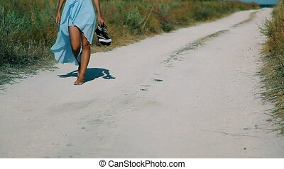 Slim girl goes by sandy road to the beach - A young girl,...