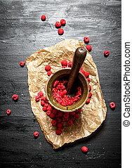 Red raspberries in a mortar with pestle.