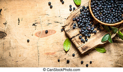 Wild blueberries in a Cup with leaves.On wooden table.
