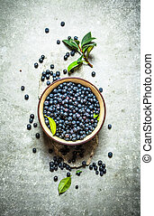 Blueberries with leaves in a Cup. On stone table.