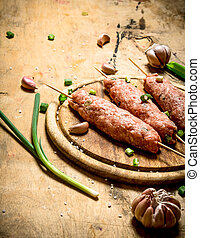 Raw kebab of beef with garlic and onions On a wooden table