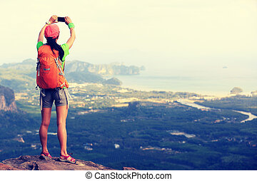 young woman hiker taking photo with smartphone on mountain...