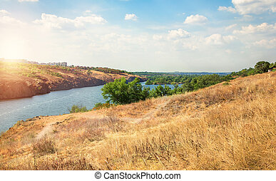 Late summer river valley, rocky hills with green trees and...