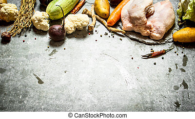 Raw chicken with the ingredients for soup.