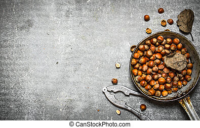 The hazelnuts in an old pan. On the stone table.