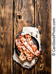 Fried bacon in a frying pan. On wooden table. - Fried bacon...
