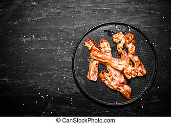 Fried bacon on a plate. On a black wooden background.