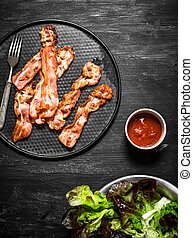 Fried bacon with sauce and greens. On a black wooden...