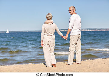happy senior couple holding hands summer beach - family,...