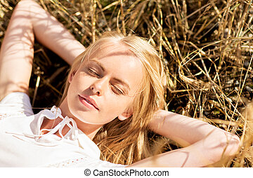 happy young woman lying on cereal field or hay - nature,...
