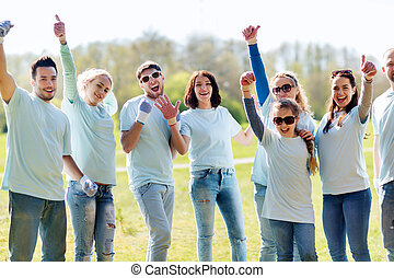 group of volunteers showing thumbs up in park -...