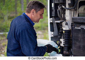 The driver who is filling in a liquid in the motor
