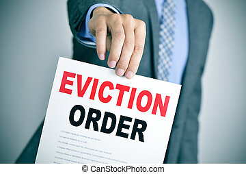 man in suit with an eviction order - a young caucasian man...
