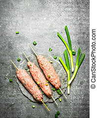 Raw kebabs on Wooden skewers with green onions. On the stone...