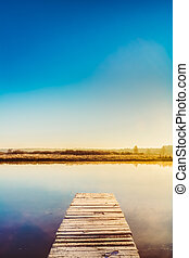 Old Wooden Boards Pier On Water Of Lake, River. Autumn Season.